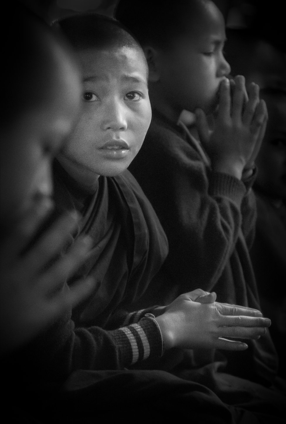A Novice Monk sits amongst his fellow devotees at Prayer in a remote Monastery near Hsipaw in Eastern Myanmar.