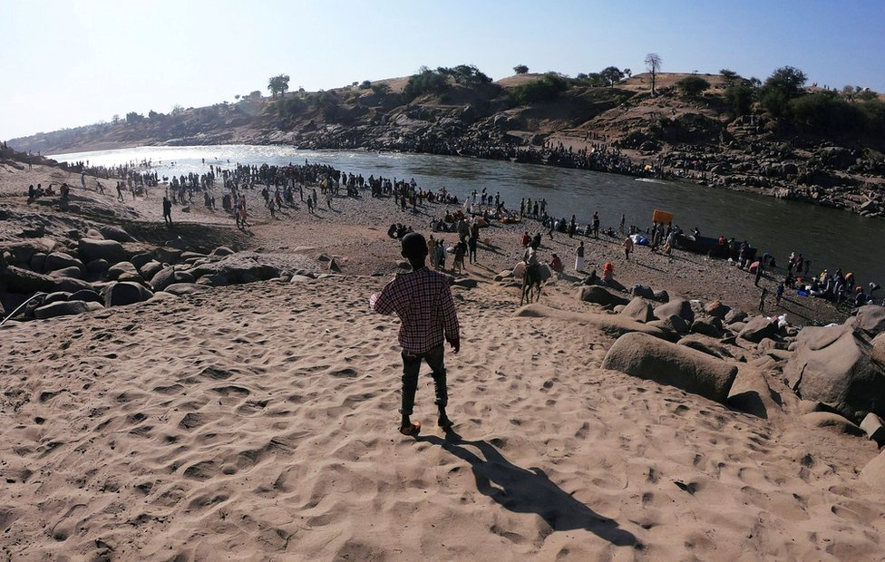 Hundreds of people walk next to and gather by the banks of the Setit River on the Sudan-Ethiopia border, on 14 November.