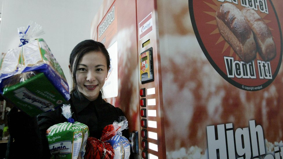 marketing executive shows some of the breads dispense from a vending machine in Singapore, 25 March 2004.