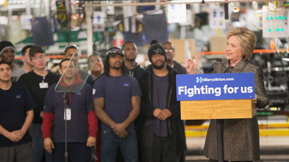 Clinton speaks on the floor of a Detroit manufacturing plant