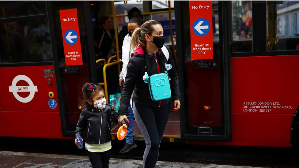 A woman and a child are seen wearing a protective face mask by a London bus