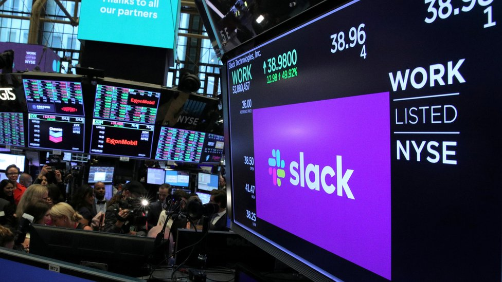 """The stock price of Slack Technologies Inc. trading under the symbol (WORK) is seen on a display above the floor of the New York Stock Exchange (NYSE) during the company""""s direct listing in New York, U.S. June 20, 2019"""