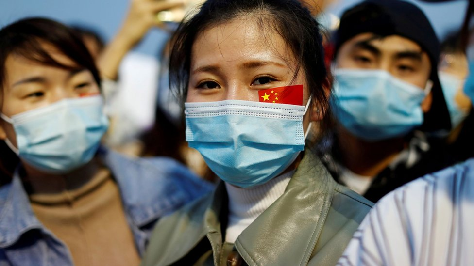 A person watches the flag raising ceremony in Beijing