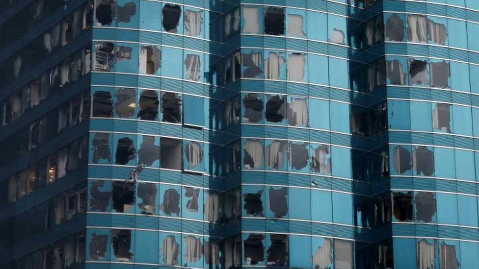 A high-rise Hong Kong building has dozens of smashed windows