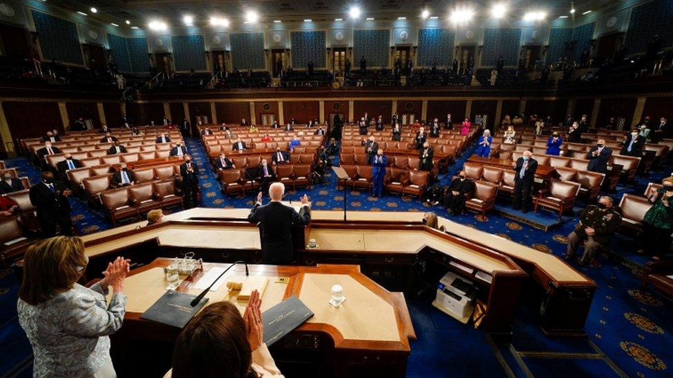 Biden de costas no púlpito, com bancadas e parlamentares à sua frente