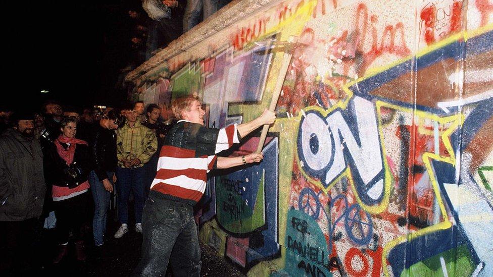 Alguien golpea el Muro de Berlín.