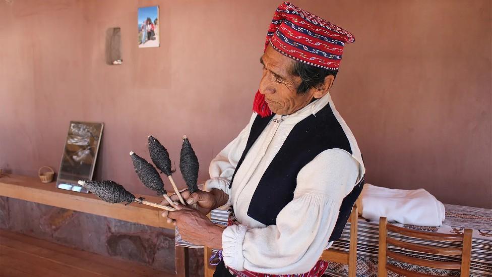 Alejandro con su sombrero mostrando la lana con la que teje