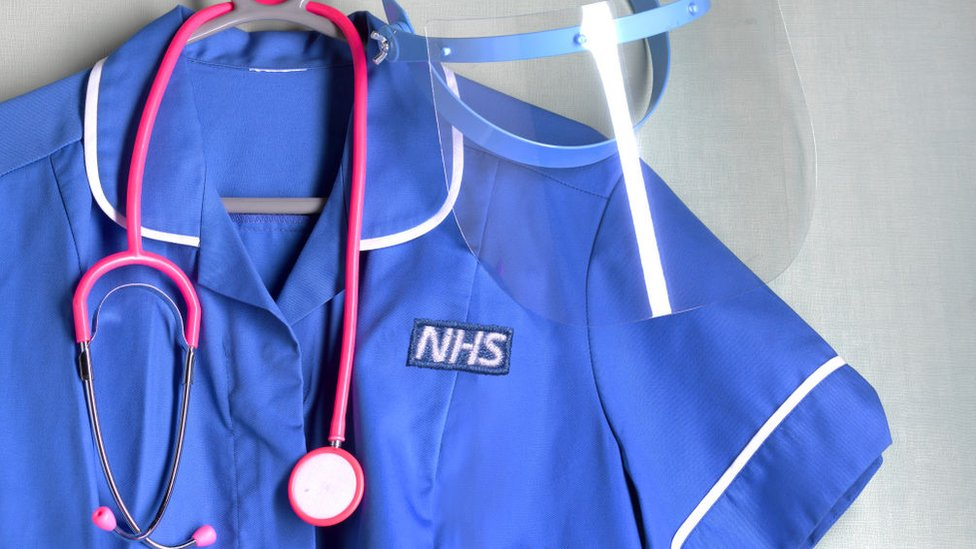 NHS nurse's uniform with PPE mask protection and a stethoscope