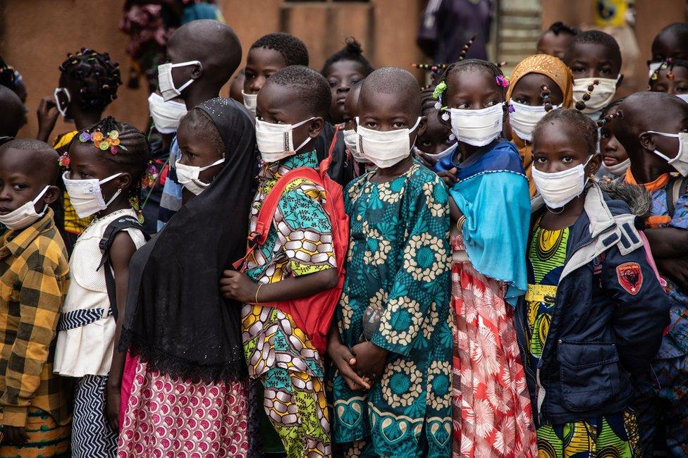 A crowd of children wearing face masks