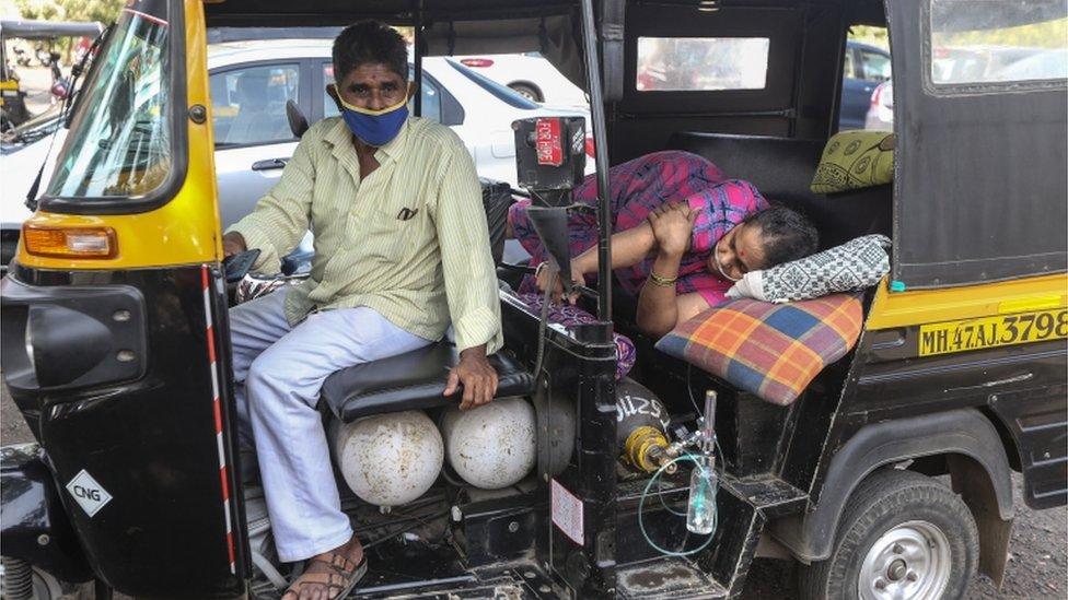 Un mujer yace en un motocarro esperando asistencia médica