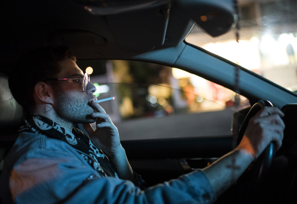 Elias smokes a cigarette whilst driving