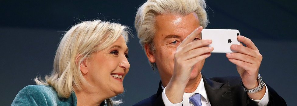 """Dutch far-right Party for Freedom (PVV) leader Geert Wilders (R) and France's far-right National Front political party leader Marine Le Pen take a selfie during a news conference at the end of the """"Europe of Nations and Freedom"""" meeting in Milan, 29 January 2016."""