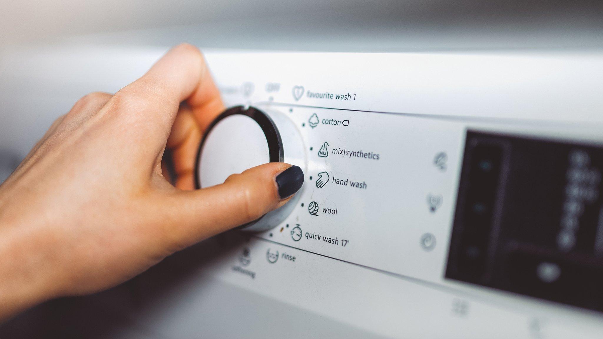 hand on washing machine controls