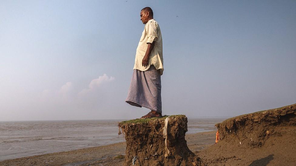 Shankar Kayal, residente de Sangar, parado en un pequeño montículo de tierra frente al mar. El resto el terreno colapsó con el avance del agua.