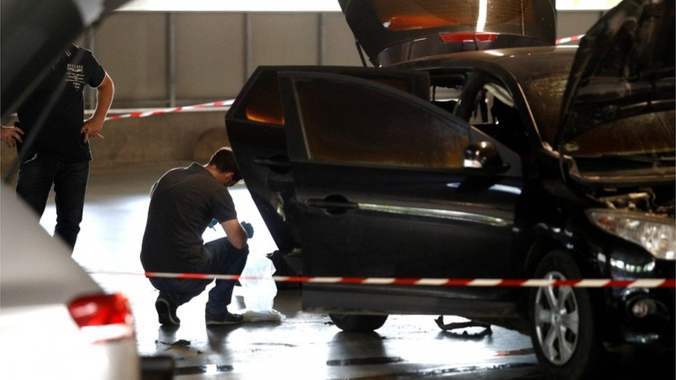 A forensic police officer crouches by a car abandoned by Redoine Faid at O'Parinor shopping mall car park