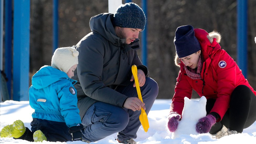 أب وأم وطفل يصنعون أشكالا من الثلج في موسكو
