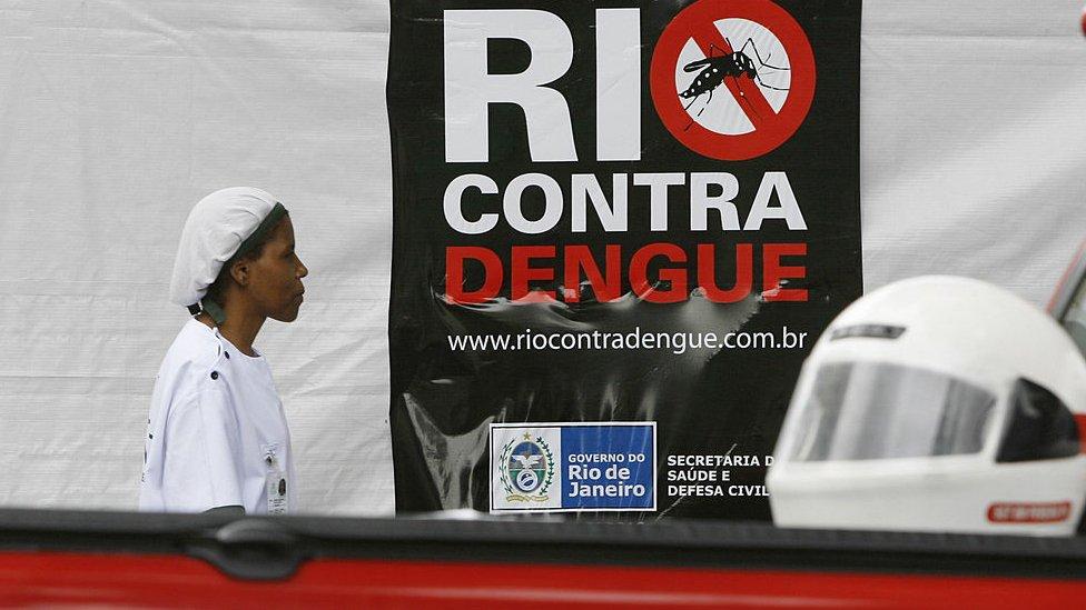 Una enfermera pasa frente a un cartel que alerta contra el dengue en Río de Janeiro