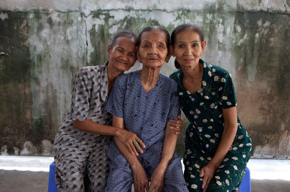 Do Thi Net sits with her daughters Nguyen Thi Ten and Nguyen Thi Sen