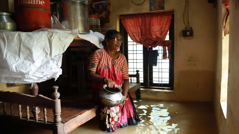 An Indian woman sits inside her house immersed in flood waters in the Ernakulam district of Kochi