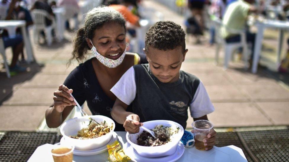 Mãe e filho comem em restaurante ao ar livre que distribui alimentos para famílias afetadas pela crise econômica em Belo Horizonte, Brasil, junho de 2020
