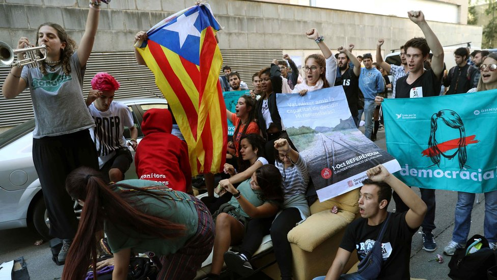 "People stage a sit-down protest in front of the Unipost delivery company""s offices in Terrassa"