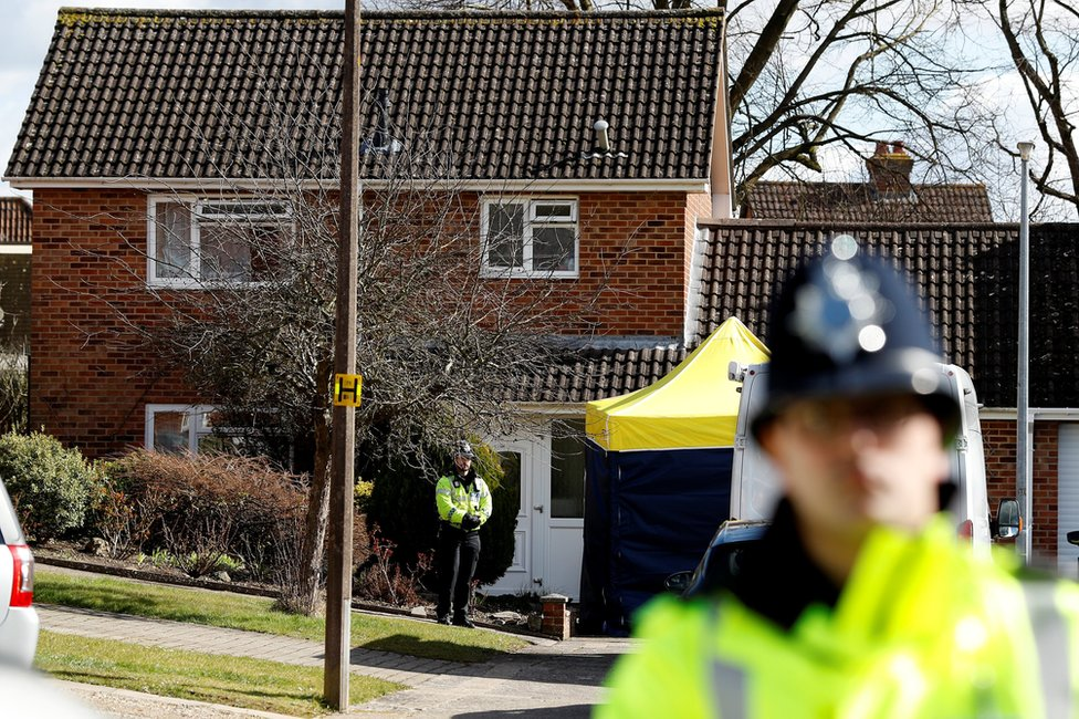Police officers stand guard outside the home of Sergei Skripal