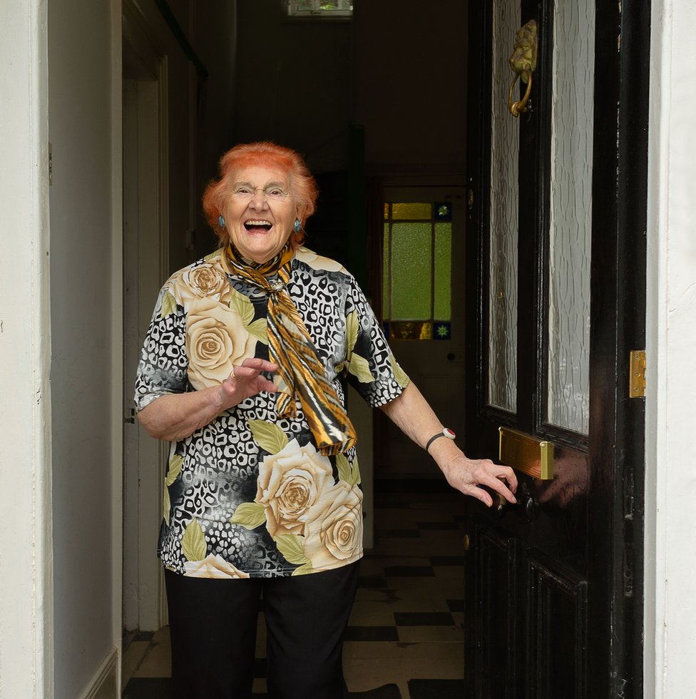Portrait of an elderly lady with red hair standing in her doorway