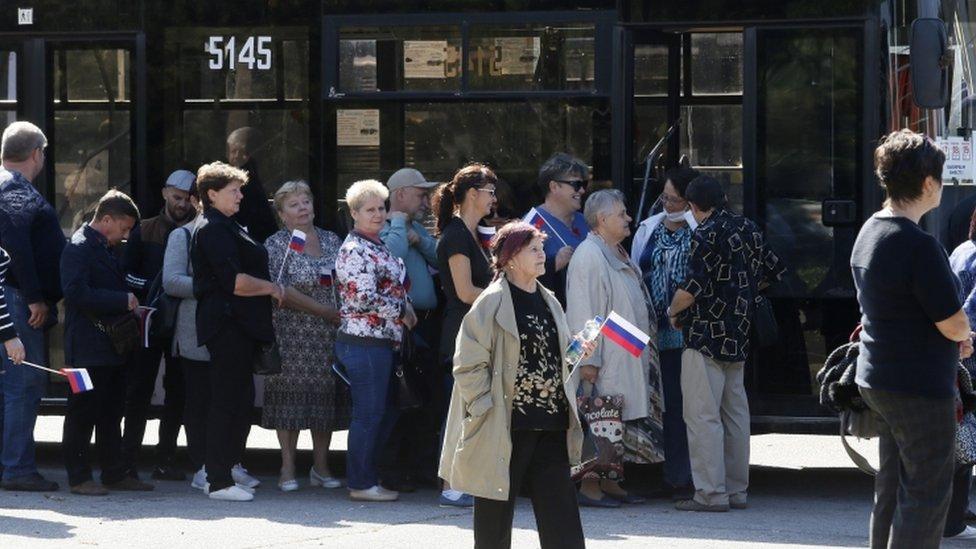 Ciudadanos rusos parten de Donetsk en los autobuses que los llevaron a votar.