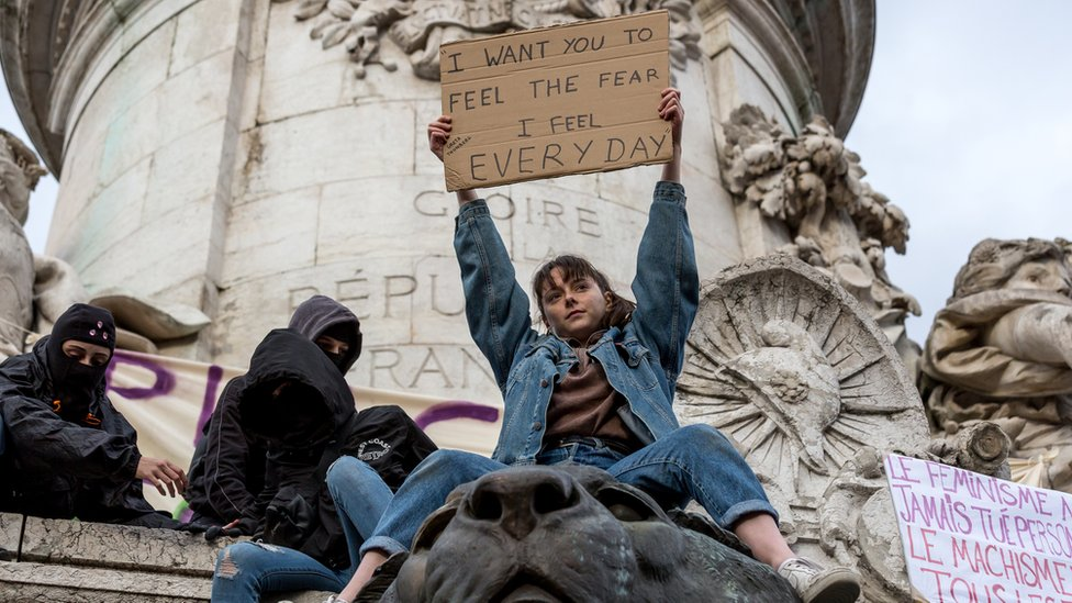 """A young woman who has climbed one of of Paris's monuments holds aloft a sign in English, reading: """"I want you to feel the fear I feel every day"""", as masked demonstrators sit nearby"""