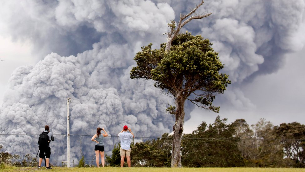 People watch as ash erupts from the Halemaumau crater near the community of Volcano during ongoing eruptions of the Kilauea Volcano in Hawaii, US on 15 May 2018.