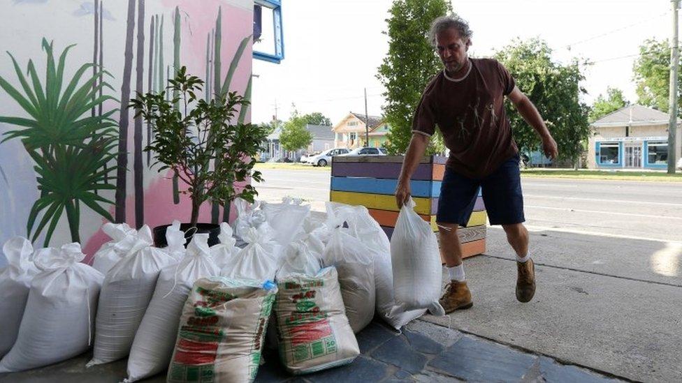 Un hombre, con bolsas de arena a la espera que la tormenta tropical Barry llegue a Nueva Orleans.