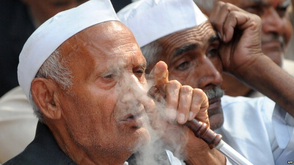 A member of the Indian 'Jat' community smokes a hukka pipe as activists take part in a protest in New Delhi on March 15, 2011.