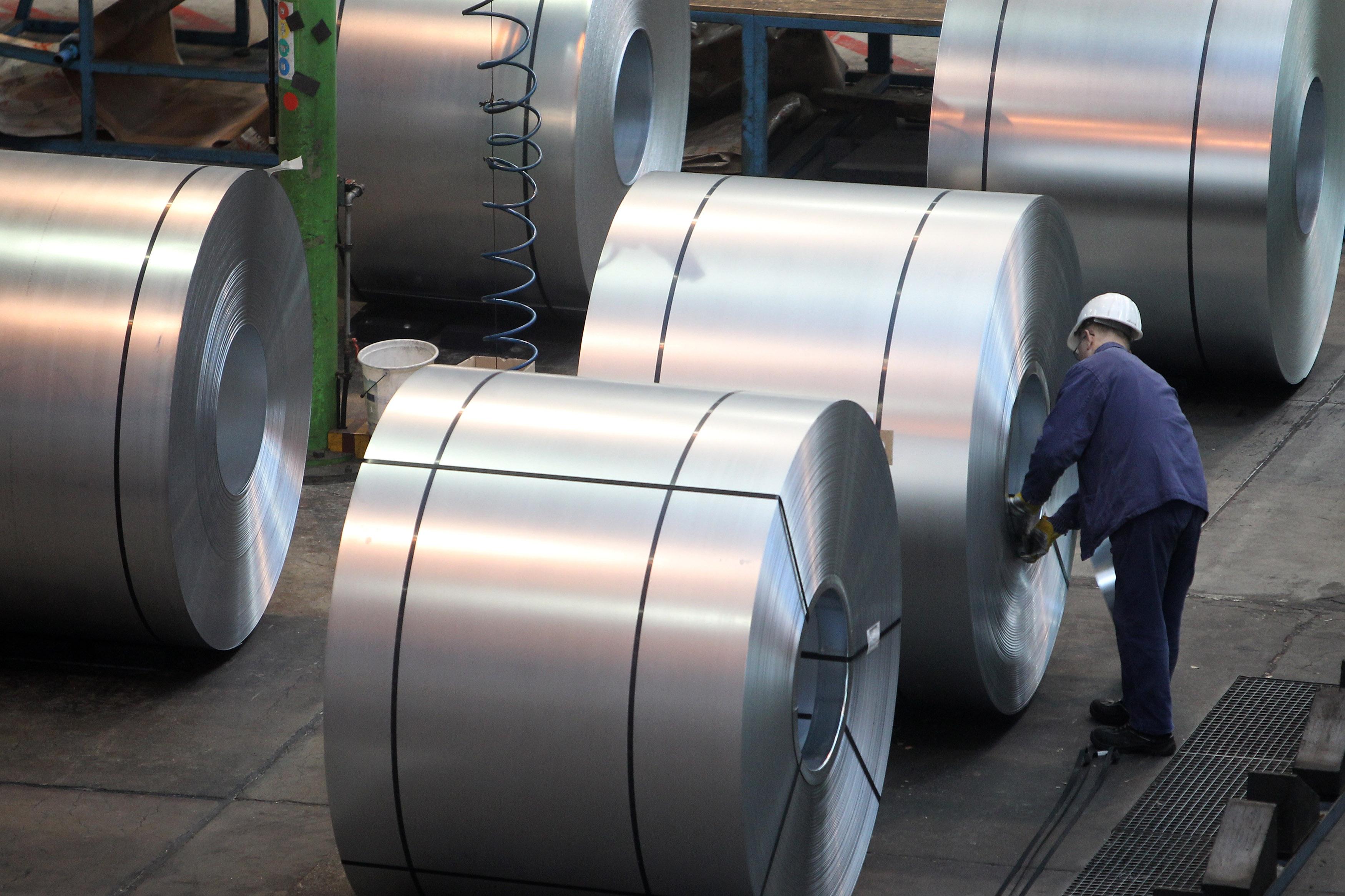 A worker inspects steel in a factory