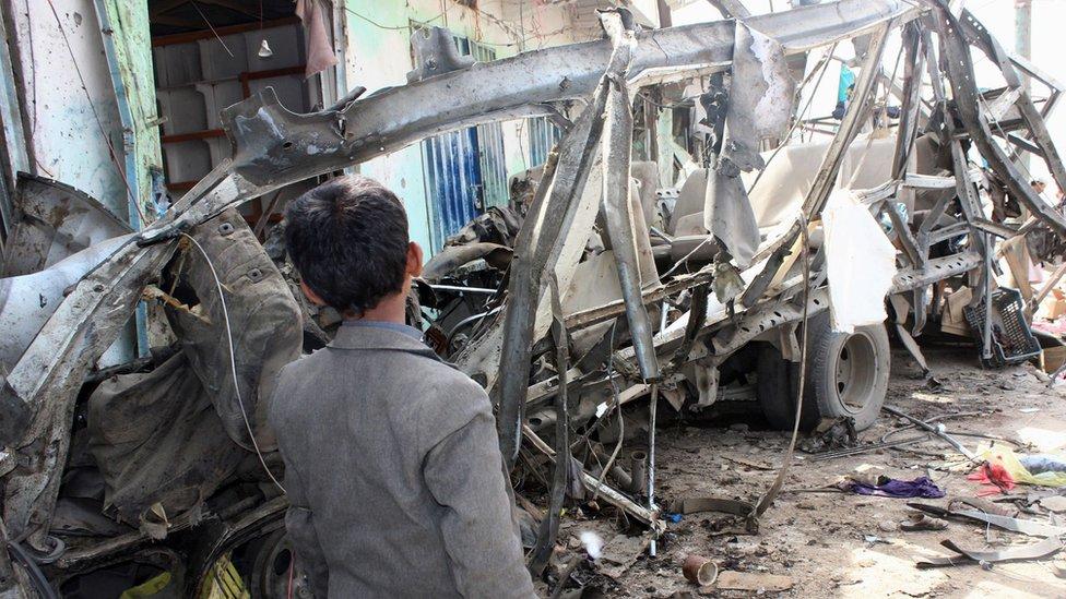 طفل يمني يقف بجانب بقايا حافلة مدرسية قصفتها طائرات التحالف في صعدة أوائل الشهر الحالي