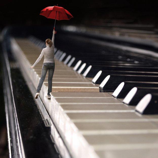 Mujer con paraguas caminando por las teclas de un piano