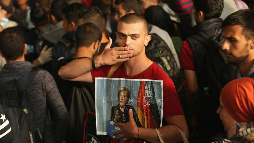 A migrant from Syria holds a picture of German Chancellor Angela Merkel as he and approximately 800 others arrive from Hungary at Munich Hauptbahnhof main railway station on September 5, 2015