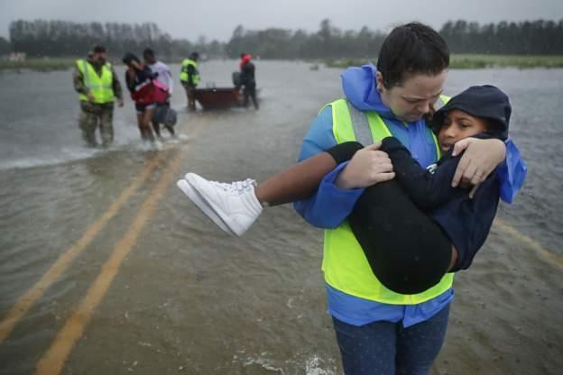 Mujer con niño en brazos en carretera inundada en Carolina del Norte.