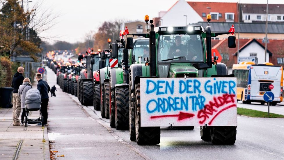 A farmer on a tractor with a placard reading 'The one who gives the order - Garbage' protests on November 14, 2020 in Aalborg, northwestern Denmark, during a rally against the Danish governments' order to cull all mink in the country.