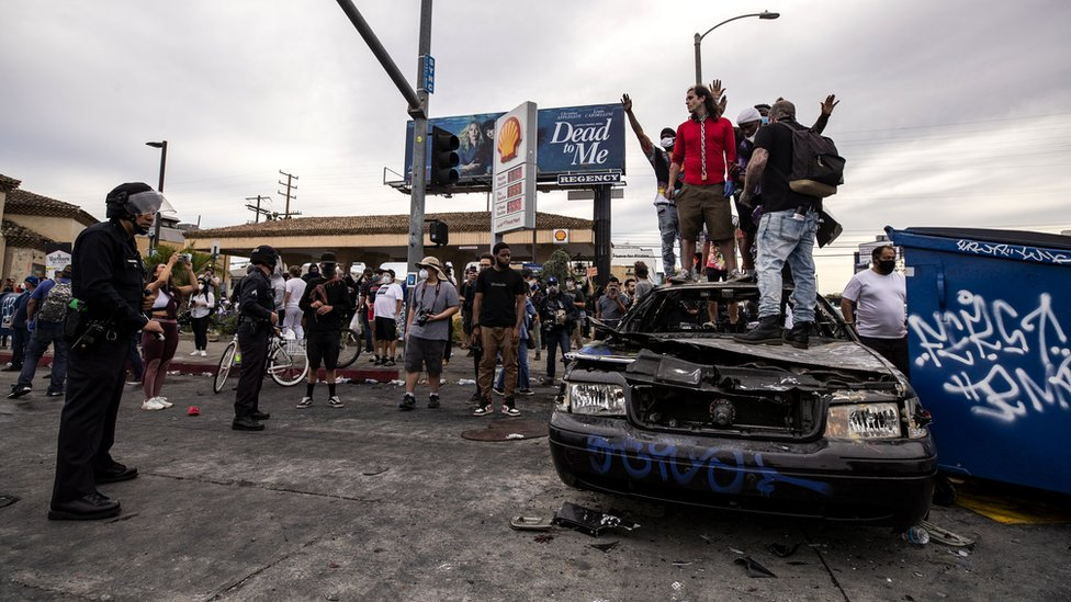 Protesters stand atop a burned out police car during protests over the Minneapolis arrest of George Floyd, who later died in police custody, in Los Angeles, California, 30 May 2020