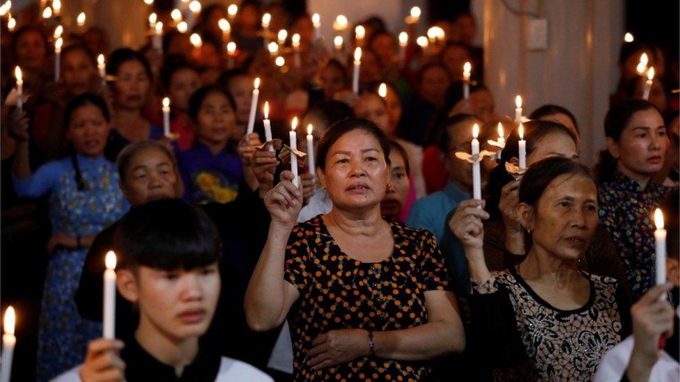 mujeres rezan con velas