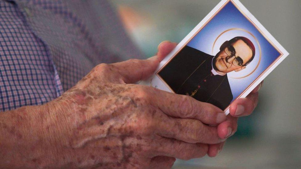 Manos sostienen una estampa de monseñor Romero.