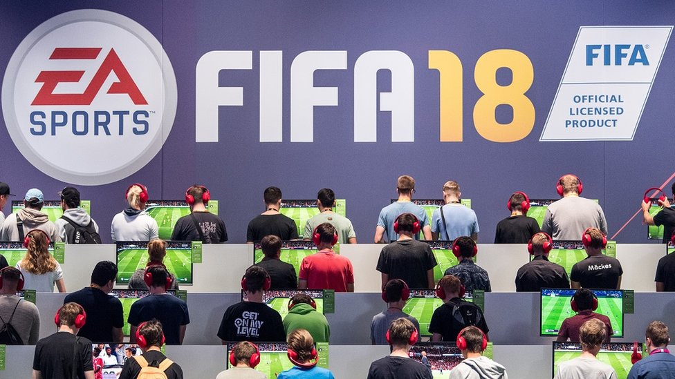 Many people are facing away from the camera playing the Fifa 18 video game. Above them, a sign reads Fifa 18.