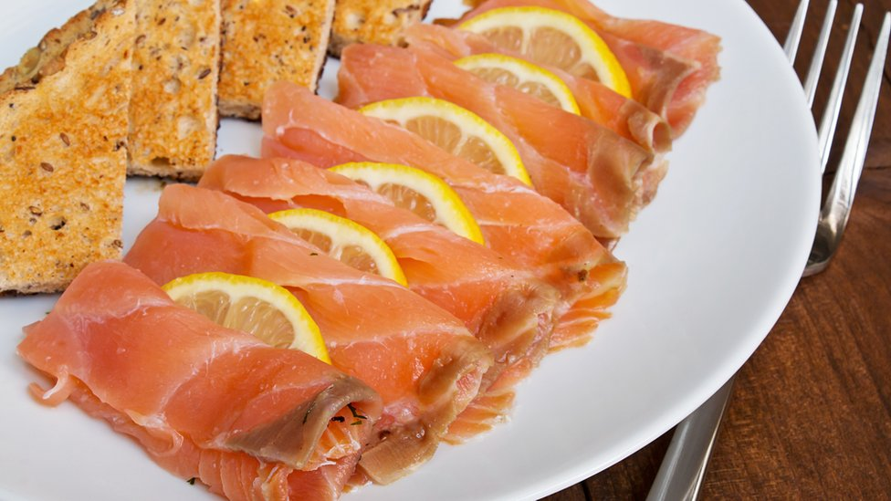 Smoked salmon and lemon on a plate with toast