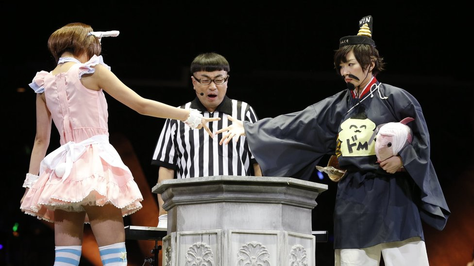 """Two women compete in the contest in 2014, with the woman on the left, in a pink dress, throwing """"scissors"""", to defeat the woman on the right, wearing a fake moustache and dressed in a bizarre re-imagining of traditional Japanese clothing."""