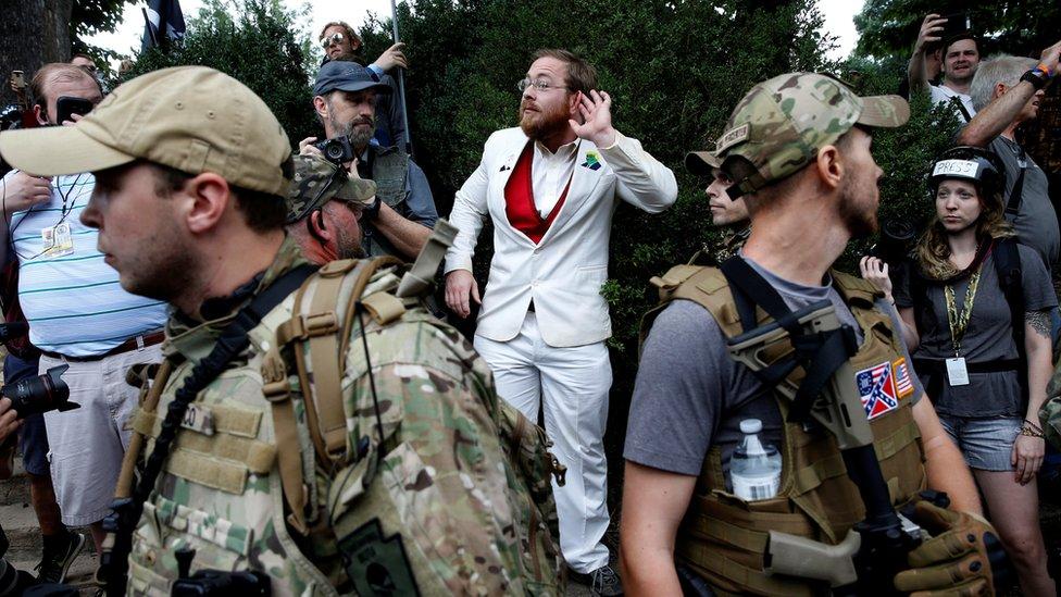 man in white suit standing behind two heavily armed men in bulletproof vests