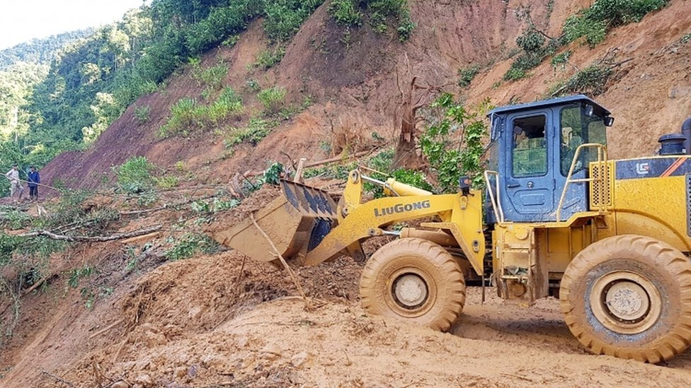 An excavator clears a road to allow access to a village that was hit by a landslide in Nam Tra My district in Quang Nam province