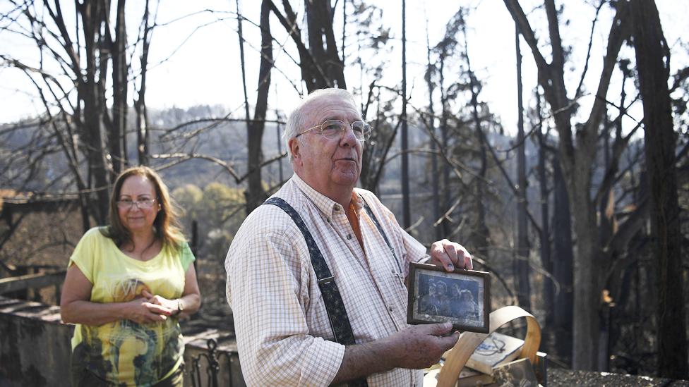 Un hombre y una mujere regresan a lo que queda de su hogar tras el incendio en Portugal en junio de 2017