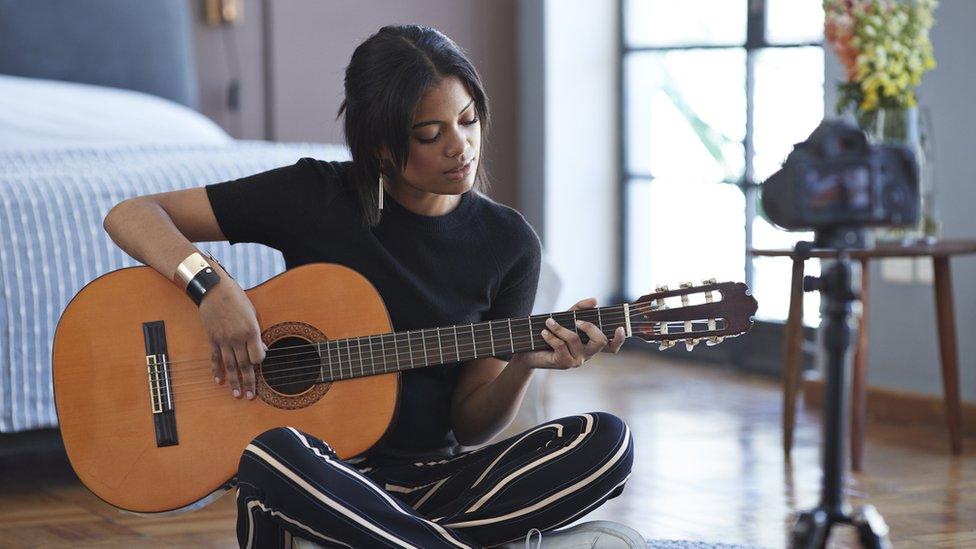 Una mujer sentada en el suelo tocando un instrumento