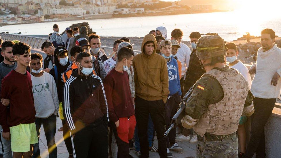 Perwira tentara Spanyol berbicara dengan imigran muda.
