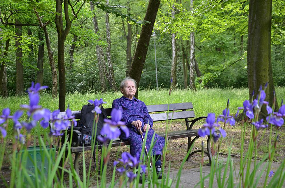 A woman sitting on a bench pin in Park Kościuszko in Katowice, Poland.